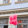 Rote Luftballons fliegen vor dem Schriftzug des Ladenlokals des Bildungswerkes in die Luft