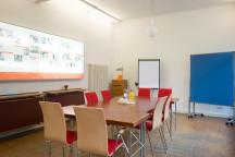 Der Seminarraum unseres Ladenlokals mit Konferenztisch, Flipchart und Pinnwand.